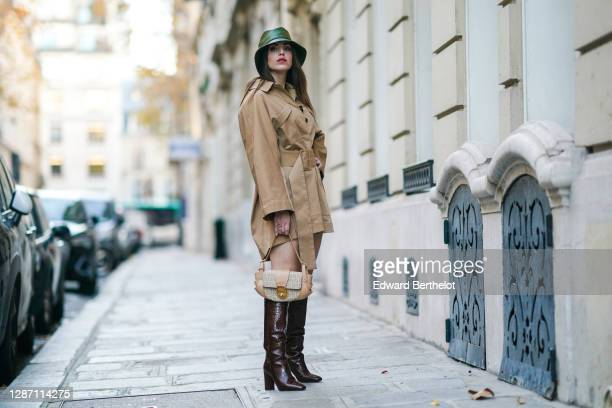 Sara Carnicella wears a green leather bag from Anthony Peto, a beige pale brown oversized dress / trench coat from Natan, a Fendi bag, brown leather...