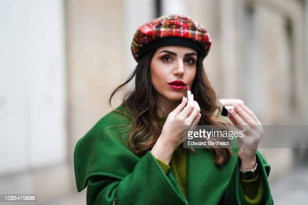 Sara Carnicella wears a green long coat with large oversized lapels from Natan, a green wool pullover from Natan, a red checked wool beret hat from...