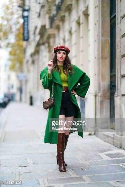Sara Carnicella wears a green long coat with large oversized lapels from Natan, a green wool pullover from Natan, a brown leather Vuitton monogram...