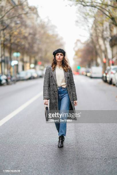 Sara Carnicella wears a Pellegrino bag, a black wool beret hat from Galleries Lafayette, a gray long checked coat from Zara, a white wool pullover...
