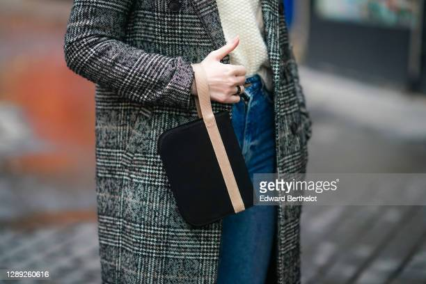 Sara Carnicella wears a Pellegrino bag, a gray long checked coat from Zara, a white wool pullover from Mango, blue denim jeans, outside the...