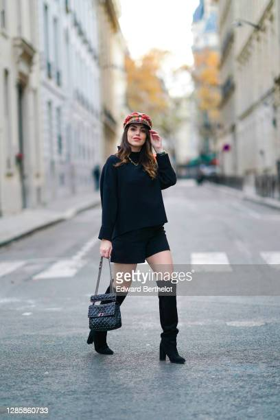 Sara Carnicella wears a red checked beret hat from Anthony Peto, a black oversized pullover from Natan, a black leather studded Valentino Rockstud...