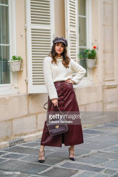 Sara Carnicella wears a tweed knitted beret hat from Chanel, a white wool pullover from Natan, a purple/burgundy leather skirt from Natan, a...