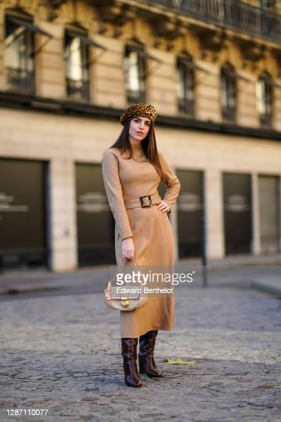 Sara Carnicella wears a yellow and black leopard print beret hat from Anthony Peto, a beige pale brown wool long dress with long sleeves and...