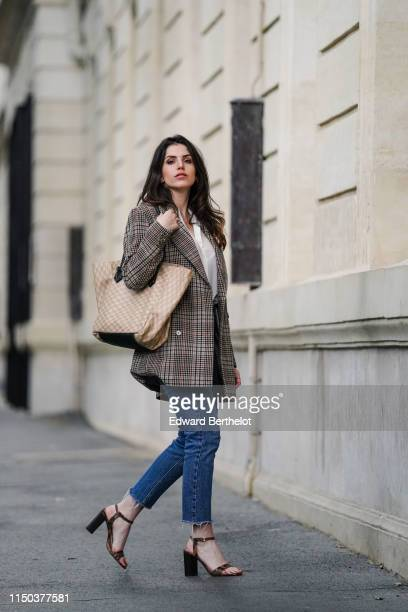 Sara Carnicella wears Jonak snake print leather shoes a beige Moreau bag a Zara checked oversized blazer jacket Bershka blue denim jeans a white...