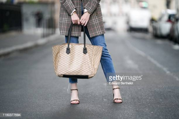 Sara Carnicella wears Jonak snake print leather shoes a beige Moreau bag a Zara checked oversized blazer jacket Bershka blue denim jeans on May 18...