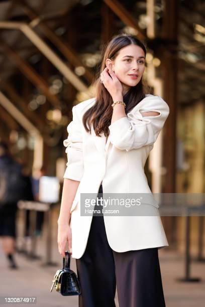Sara Crampton wearing Christopher Esber white blazer black wide pants and Rylan bag and bracelet at Afterpay Australian Fashion Week 2021 on May 31,...