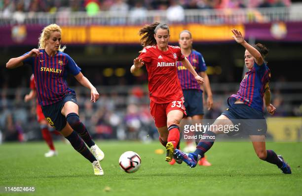 Sara Dabritz of Bayern Munich is challenged by Kheira Hamraoui of Barcelona and Marta Torrejon of Barcelona during the UEFA Women's Champions League...