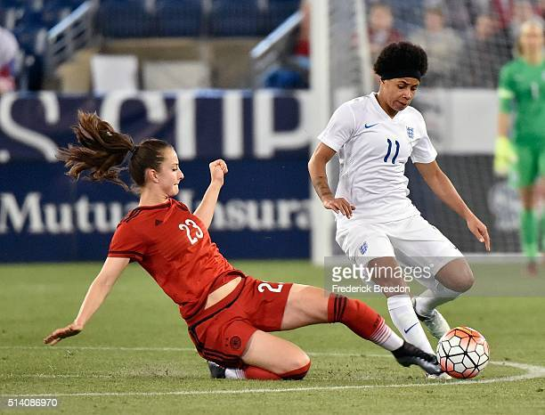 Sara Dbritz of Germany slides under Demi Stokes of England during the second half of a friendly international match in the Shebelieves Cup at Nissan...
