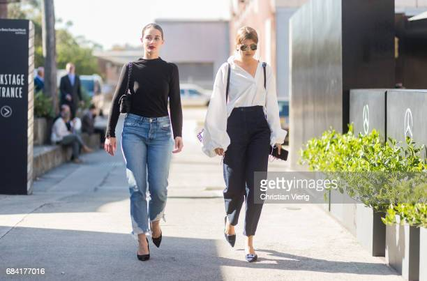 Sara Donaldson wearing a black knit blue denim jeans heels and Talisa Sutton wearing a white button shirt with wide sleeves navy pants black bag at...