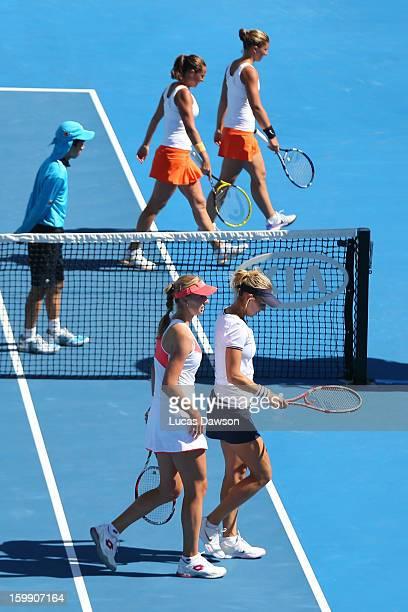 Sara Errani of Italy and Roberta Vinci of Italy and Ekaterina Makarova of Russia and Elena Vesnina of Russia walk off court during a break between...