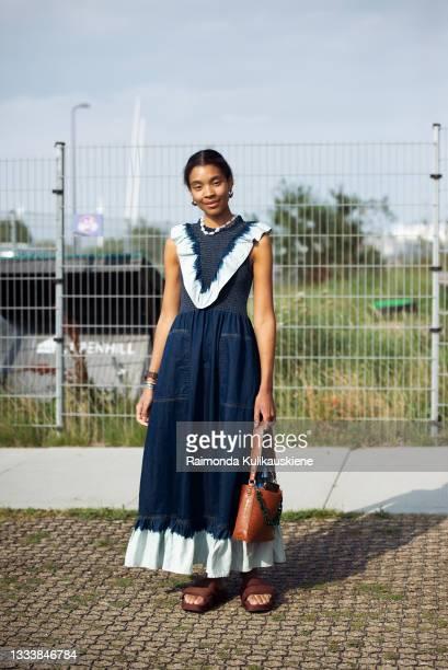 Sara Flaaen Licius wearing long denim dress outside Ganni during Copenhagen fashion week SS22 on August 12, 2021 in Copenhagen, Denmark.