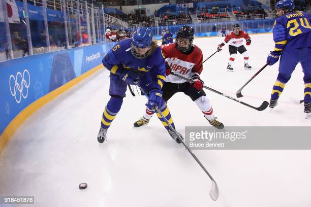 Sara Hjalmarsson of Sweden and Shiori Koike of Japan battle for the puck in the first period during the Women's Ice Hockey Preliminary Round - Group...