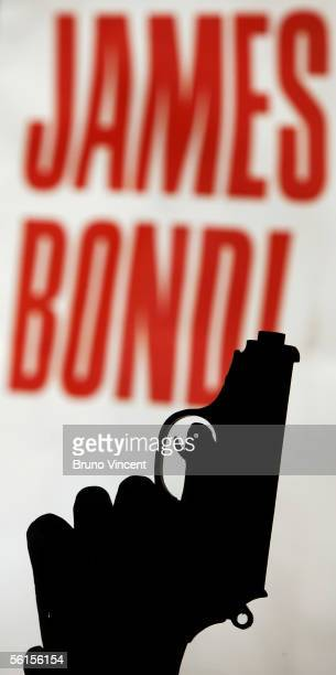 Sara kuwaharh an assistant from Bonhams auctioneers models a replica Walther PPK gun used in the Bond film 'On Her Magesty's Secret Service' on...