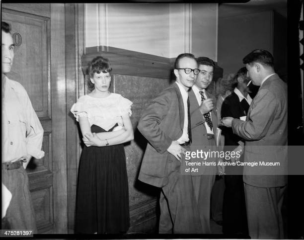 Sara Louise Gordon, and men Including Gilbert Helwig wearing eyeglasses, standing in hallway outside of Criminal Court No 3, in Allegheny County...