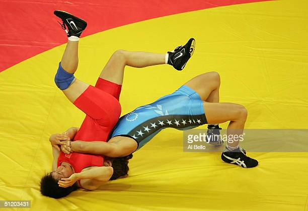 Sara McMann of the USA flips Lili Meng of China during the women's Freestyle wrestling 63 kg elimination round on August 22, 2004 during the Athens...