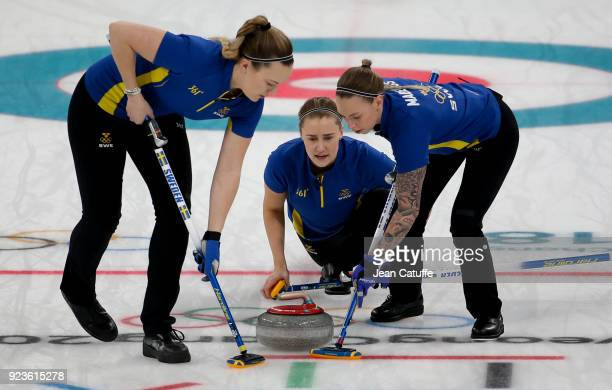 Sara McManus of Sweden throws a stone surrounded by teammates Agnes Knochenhauer and Sofia Mabergs during the women's curling semifinal game between...