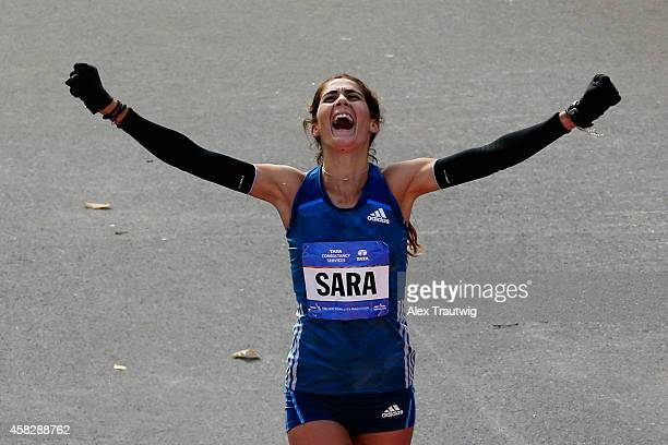 Sara Moreira of Portugal celebrates as she crosses the finish line to finish third in the Pro Women's division during the 2014 TCS New York City...