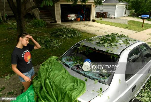 Sara Pilot left looks at the hail damage to her father's car outside of her home from a large hailstorm that raced through their neighborhood the...
