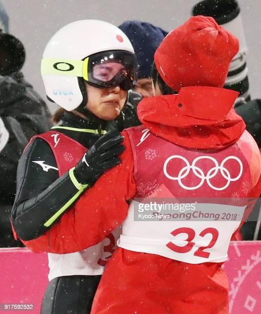 Sara Takanashi of Japan bursts into tears hugged by the teammate Yuki Ito after her second jump in the women's normal hill individual ski jumping at...