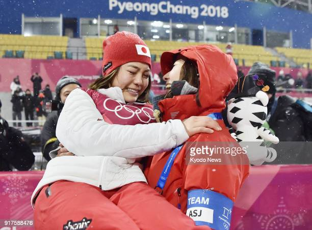 Sara Takanashi of Japan bursts into tears in the arms of her coach Izumi Yamada after winning the bronze medal in the women's normal hill individual...