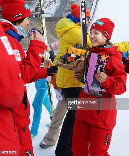 Sara Takanashi of Japan chats with her teammate Yuki Ito after the victory ceremony at the women's ski jumping World Cup event in Oberstdorf Germany...