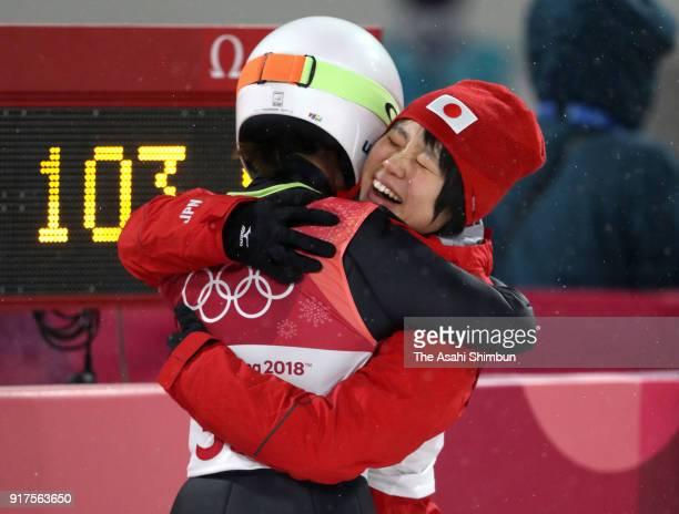 Sara Takanashi of Japan is congratulated by her team mate Yuki Ito as her medal is confirmed after competing in the second jump during the Ladies'...