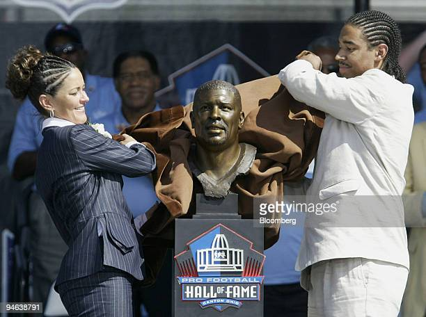 Sara White, left, wife of late Hall of Fame inductee Reggie White, and their son Jeremy unveil a bust of Reggie White during his induction into the...