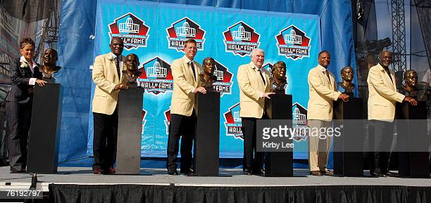 Sara White Reggie White's wife Harry Carson Troy Aikman John Madden Warren Moon and Rayfield Wright pose with busts at NFL Pro Football Hall of Fame...