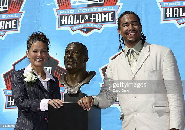 Sara White wife of the late Reggie White and Jeremy White son pose with Reggie's bust after his induction during the Class of 2006 Pro Football Hall...