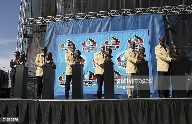 Sara White wife of the late Reggie White Harry Carson Troy Aikman John Madden Warren Moon and Rayfield Wright pose with their busts' after their...