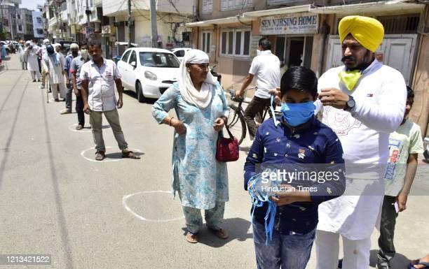 Sarabjeet Singh president of Shaheed Bhagat Singh Welfare Club Punjab ties a face mask to a child amid lockdown, in Katra Sher Singh, near Telephone...