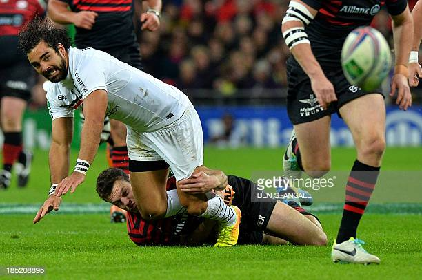 Saracens' centre Duncan Taylor tackles Toulouse wing Yoann Huget during the European cup rugby union match between Saracens and Toulouse at Wembley...