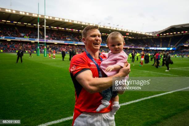 Saracens' English wing Chris Ashton holds his baby Ava as he celebrates on the pitch after the rugby union European Champions Cup Final match between...