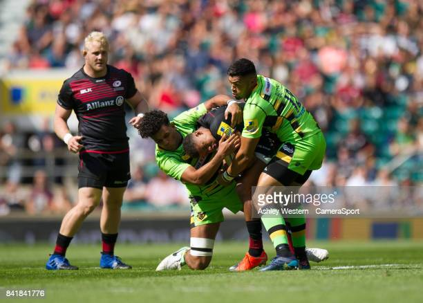 Saracens' Nathan Earle is tackled by Northampton Saints' Lewis Ludlam and Luther Burrell during the Aviva Premiership match between Saracens and...