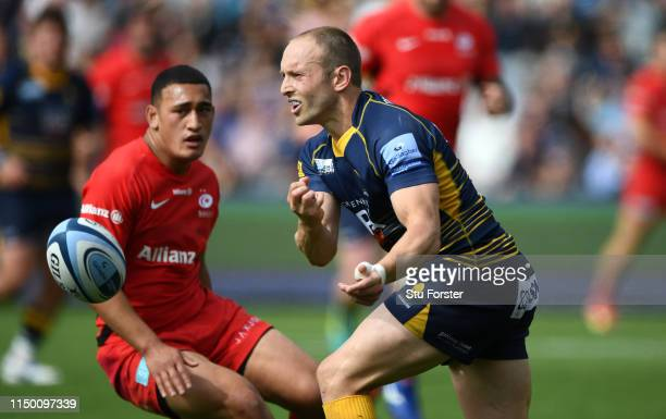 Saracens player Manu Vunipola looks on as Chris Pennell of the Warriors passes the ball during the Gallagher Premiership Rugby match between...