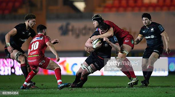 Saracens player Mark Flanagan runs with the ball into Rynier Bernardo of the Scarlets during the Anglo-Welsh Cup match at Parc y Scarlets on January...