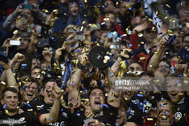 TOPSHOT Saracens' players celebrate with the trophy after winning the European Champions Cup final rugby union match between Racing 92 and Saracens...
