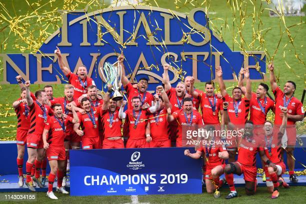 Saracens' South African-born English centre Brad Barritt lifts the trophy as Saracens' players celebrate their win on the field after the European...