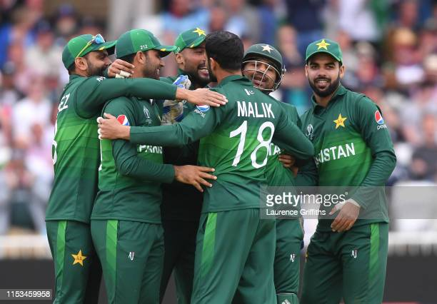 Sarafaz Ahmed of Pakistan congratulates bowler Shoaib Malik after claiming the wicket of Ben Stokes of England during the Group Stage match of the...