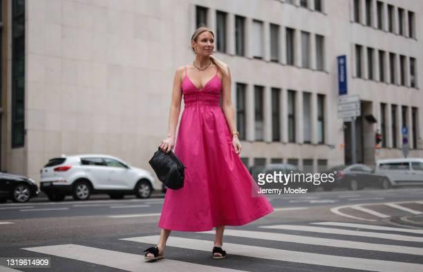 Sarah Achterholt wearing pink Zara dress, black Isabel Marant pouch bag and black Manebi slides via The Wants Shoes on May 12, 2021 in Cologne,...
