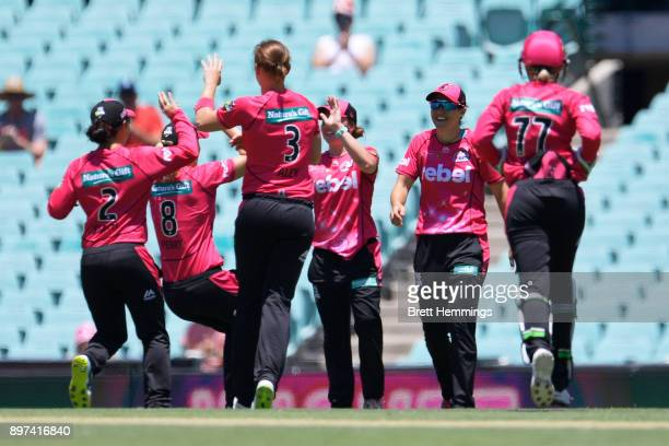 Sarah Aley of the Sixers celebrates with team mates after taking the wicket of Lauren Winfield of the Hurricanes during the Women's Big Bash League...