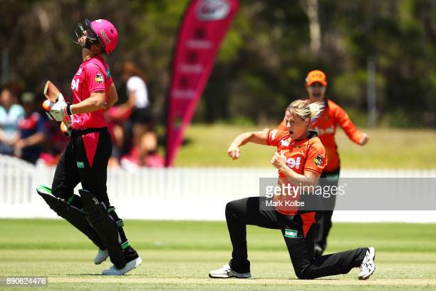 Sarah Aley of the Sixers looks dejected as Katherine Brunt of the Scorchers celebrates her wicket during the Women's Big Bash League match between...