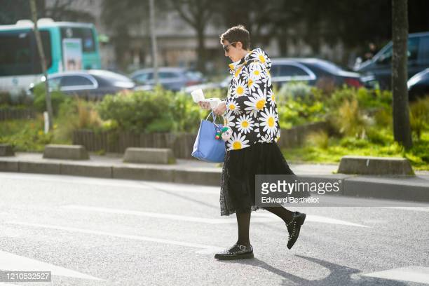 Sarah Andelman wears sunglasses, a floral print coat with a hood, a blue bag, a black lace mesh skirt, black studded shoes, outside Lacoste, during...