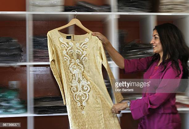 CAJON CA Sarah Ansari the founder and CEO of Artizara Inc carries a dress from her new fall collection in her clothing warehouse in El Cajon CA on...