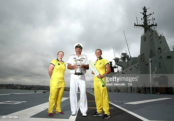 Sarah Beard and Ashleigh Gardner pose with HMAS Canberra's Engineering Officer Commander Guy Lewis aboard the HMAS Canberra during a Cricket...