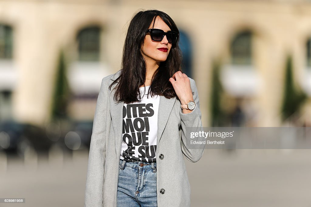 Sarah Benziane, fashion and life style blogger @lescolonnesdesarah, is wearing a French Do It Water white t-shirt with the inscription 'dites moi que je suis bonne', New Look blue denim jeans, Zara yellow shoes, a New Look gray long coat, a Saint Laurent YSL bag, and sunglasses, on December 10, 2016 in Paris, France.