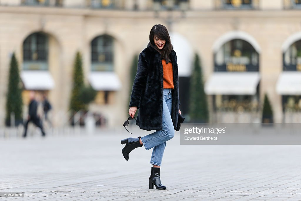 Sarah Benziane, fashion and life style blogger @lescolonnesdesarah, is wearing a New Look faux fur black coat, a New Look orange pull over, New Look blue denim jeans, a New Look black clutch with floral print, New Look black shoes, and sunglasses, at Place Vendome, on December 10, 2016 in Paris, France.