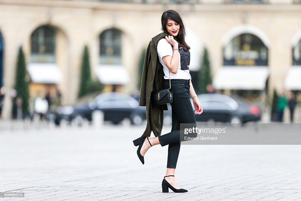 Sarah Benziane, fashion and life style blogger @lescolonnesdesarah, is wearing a Made In Toulouse white t-shirt with the inscription 'Hein ?', a New Look green khaki long coat, The Kooples black denim jeans, Mango black shoes, and a Saint Laurent YSL black bag, at Place Vendome, on December 10, 2016 in Paris, France.