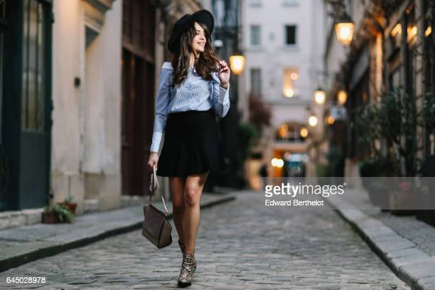 Sarah Benziane fashion and life style blogger wears a black hat a Newlook blue striped top a Cache Cache black skirt Newlook snake print boots and an...